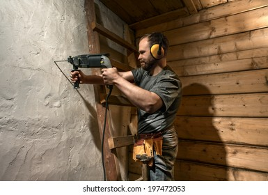 construction worker drill perforate concrete wall on wood background
