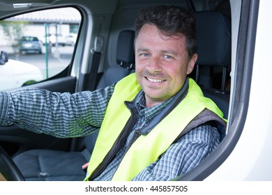 Construction worker driving a car. He is smiling