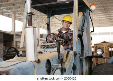 A construction worker driving an earth mover on a construction site.