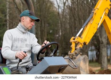 Construction worker driving road roller on backhoe equipment background