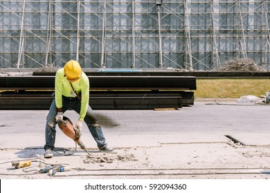 Construction worker  electric drill Drilling concrete ground in construction area