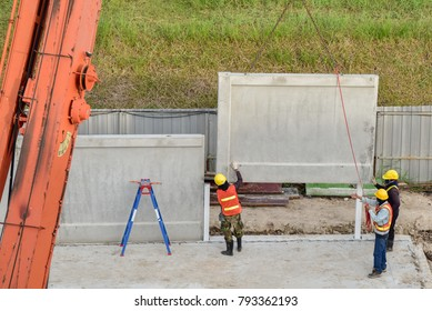 Construction worker and engineer looking  mobile crane up lift precast concrete wall in new construction warehouse site