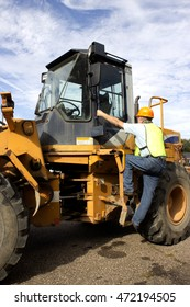 A construction worker enters a large skid loader to start the day.
