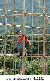 A construction worker erecting bamboo scaffolding at a building construction site in Hong Kong.