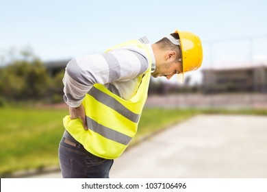 Construction worker feeling backpain in lumbar area pressing painful lower back and leaning forward