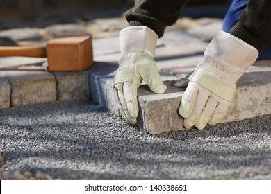 Construction worker fixing the pavestone on the road