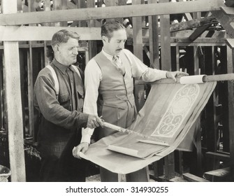 Construction worker going over plans with architect