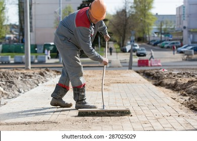 Construction worker grouting dry sand with brush into paver bricks joints during road works