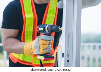 construction worker or handyman working with a drill machine at construction site