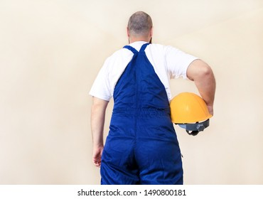 Construction worker and handyman is working on renovation of apartment. Builder at construction site with protective uniform and equipment, he with suit, coverall and yellow helmet holding in hand.