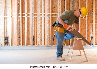 Construction worker in hard hat sawing timber on building site