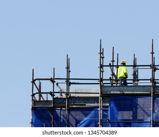 Construction Worker in a hard hat working among the scaffolding on the top floor of multistory new home units building.