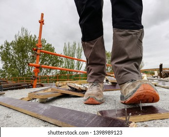 A construction worker has an accident while walks through a site with debris and stepping on a nail