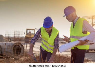 Construction worker with helmet working on reinforcement mesh at building site and engineer talking to him