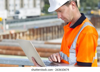 Construction worker with helmet working outdoor at a building site for a new road