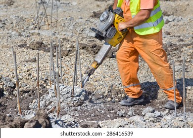 Construction worker holding jackhammer and breaking reinforced piles in the ground
