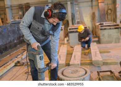 construction worker holding jackhammer and breaking reinforced concrete