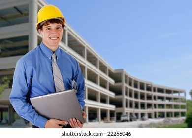 Construction Worker Holding Laptop in front of a Commercial Construction Building