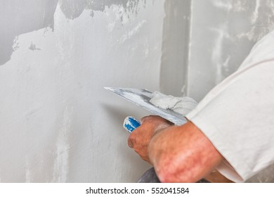 Construction worker holding plastering trowel, smoothing wall defects.