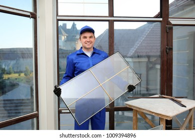 Construction worker holding window glass indoors