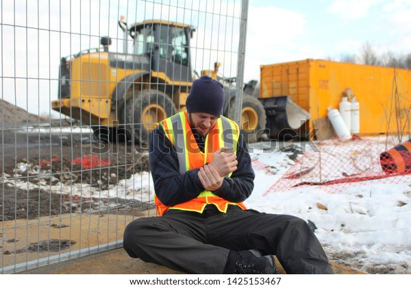 Construction worker with injured wrist at a job site in the winter