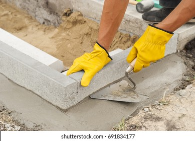 construction worker install curbs for paving slabs