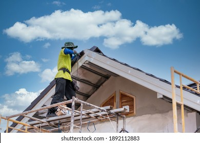 Construction worker install new ceramic tile roof, Roofing tools, Electric drill used on new roofs on construction site.