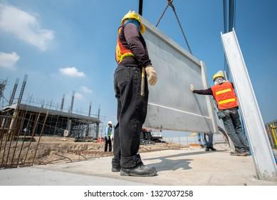 Construction worker installation precast concrete panel at construction site