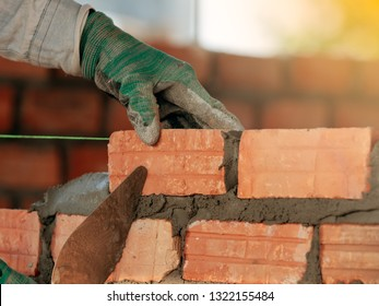 Construction worker installing bricks in construction site