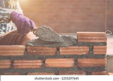 Construction worker installing bricks wall in process of house building