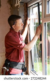 Construction Worker Installing New Windows In House