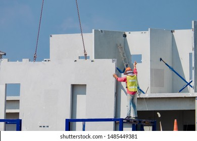 Construction worker are installing the precast concrete wall, orange safety helmet and green vest.