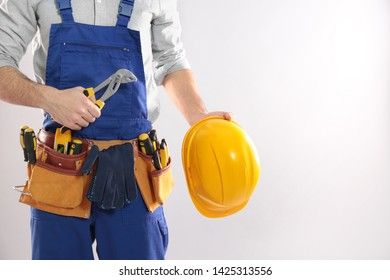 Construction worker with instrument, hard hat and tool belt on light background, closeup. Space for text