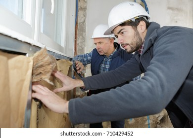 construction worker insulating house walls