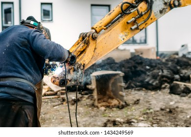 Construction worker, laborer, welding excavator arm with arc welding machinery