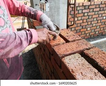 Bauarbeiter, der Ziegel auf dem Baugelände legt.
