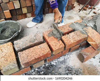 construction worker laying bricks at constrction site.