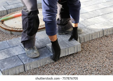 Construction worker laying cobblestones, paving stones