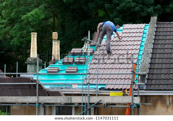 Construction Worker Laying New Roofing Tiles On A Domestic House