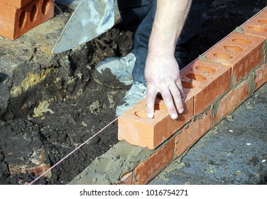 Construction worker lays bricks building house extension.