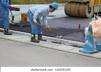 Construction worker leveling asphalt.