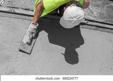 Construction worker leveling concrete pavement.