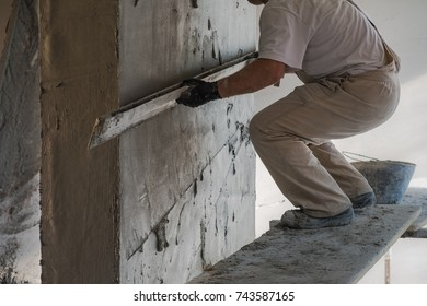 Construction worker leveling the wall surface of cement plaster