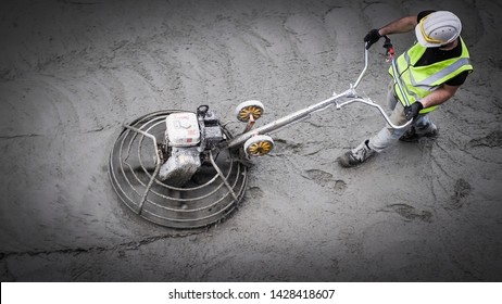 Construction worker levelling and troweling fresh concrete on construction site