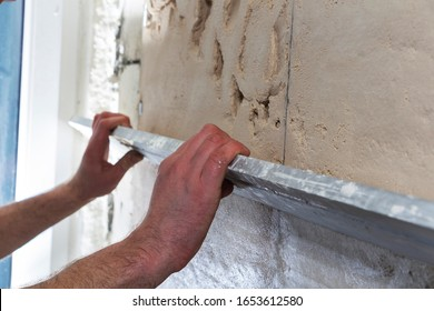 Construction worker with a long spatula to plaster the wall by hand.