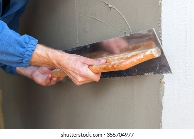 Construction worker with long trowel plastering a wall