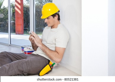 Construction worker looking in cellphone while sitting