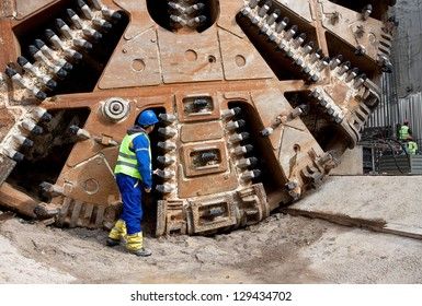 Construction worker looking at tunnel boring machine cutter head