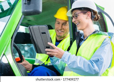 Construction worker in construction machinery discussing with engineer blueprints on pad or tablet computer on site