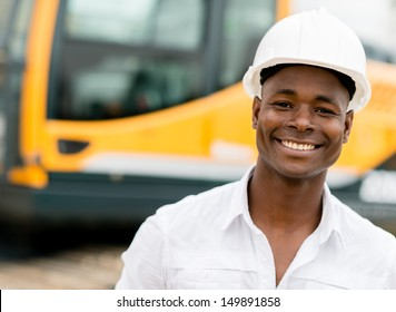 Construction worker with machines at the background looking happy